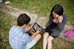 Students outside on the grass with iPads