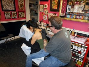 Tattoo artist Bill Stevenson works on Jacqui's tattoo.