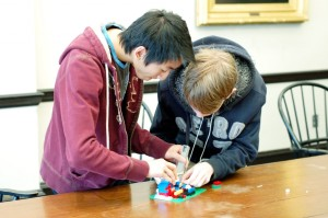 Students add a 3D printed arm to their Lego catapult design.