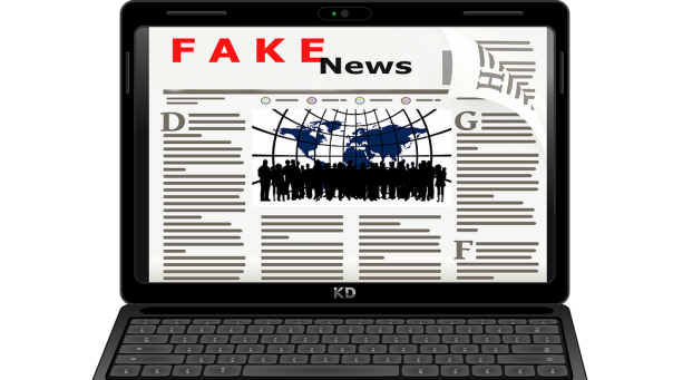 "laptop computer displaying a news website with the heading ""fake news"""
